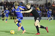 AFC Wimbledon striker Lyle Taylor (33) battles for possession with Wigan Athletic defender Dan Burn (33) during the EFL Sky Bet League 1 match between AFC Wimbledon and Wigan Athletic at the Cherry Red Records Stadium, Kingston, England on 16 December 2017. Photo by Matthew Redman.