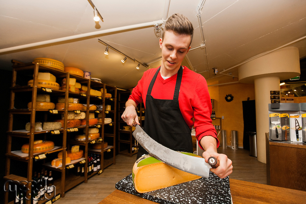 Young store clerk cutting cheese at counter