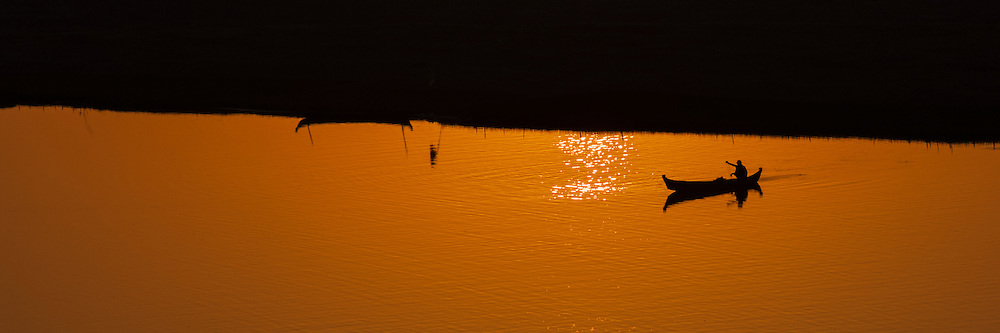 Man rowing across river after sunset with silhouette of boat