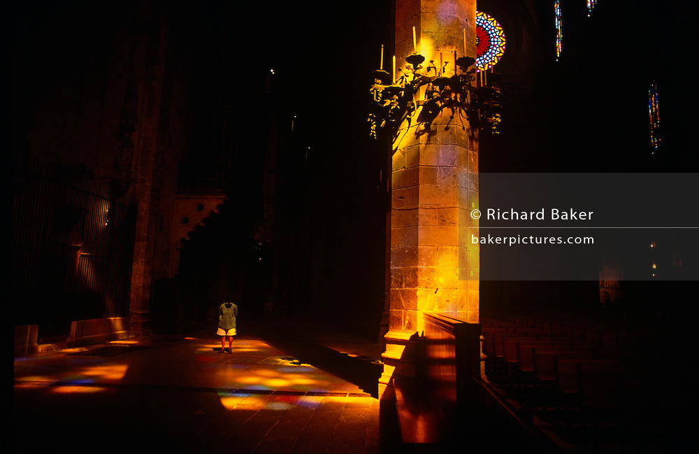 Stained glass light shines on to 44-meter tall octagonal pillars, visitors and the floor of Palma's La Seu Cathedral