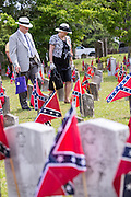 Descendants of Civil War soldiers walks past grave markers decorated with Confederate Flags following a ceremony marking Confederate Memorial Day at Magnolia Cemetery April 10, 2014 in Charleston, SC. Confederate Memorial Day honors the approximately 258,000 Confederate soldiers that died in the American Civil War.