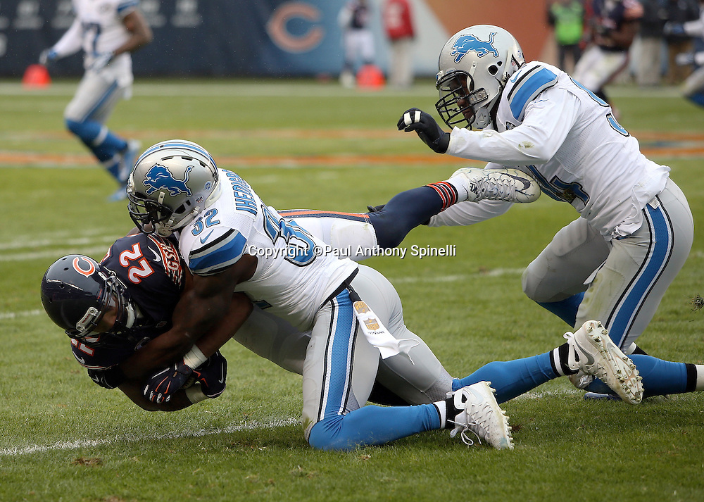Detroit Lions strong safety James Ihedigbo (32) and Detroit Lions defensive end Ezekiel Ansah (94) tackle Chicago Bears running back Matt Forte (22) after Forte catches a second quarter pass for a gain of 6 yards during the NFL week 17 regular season football game against the Chicago Bears on Sunday, Jan. 3, 2016 in Chicago. The Lions won the game 24-20. (©Paul Anthony Spinelli)