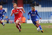 Tareiq Holmes-Dennis of Oldham Athletic runs at Liam O'Neil of Chesterfield  during the Sky Bet League 1 match between Oldham Athletic and Chesterfield at Boundary Park, Oldham, England on 28 March 2016. Photo by Simon Brady.