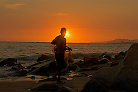 The fisherman fishes on the beach of Puerto Vallarta ,Mexico during  a beautiful sunset.