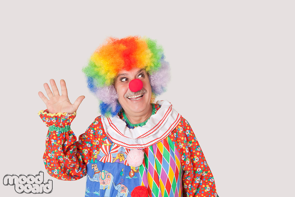 Cheerful senior male clown waving hand while looking away over gray background