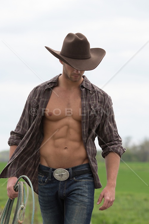 sexy cowboy with an open shirt walking on a ranch