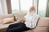 Senior man reading book on sofa in house