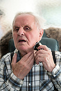 90+ years old man shaving himself with a cordless electric razor