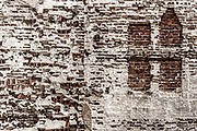 A variety of bricks and mortar present interesting shapes and textures in this composition.  A mix of sepia tone and select color additions from the original image where applied in post processing.