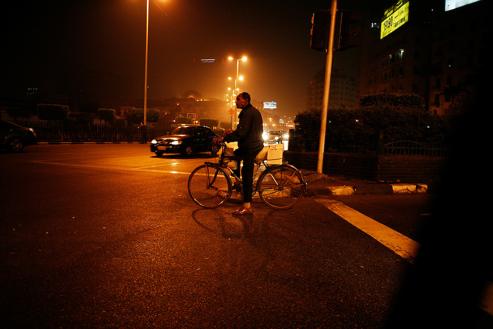 A man rides a bicycle in Cairo at night.