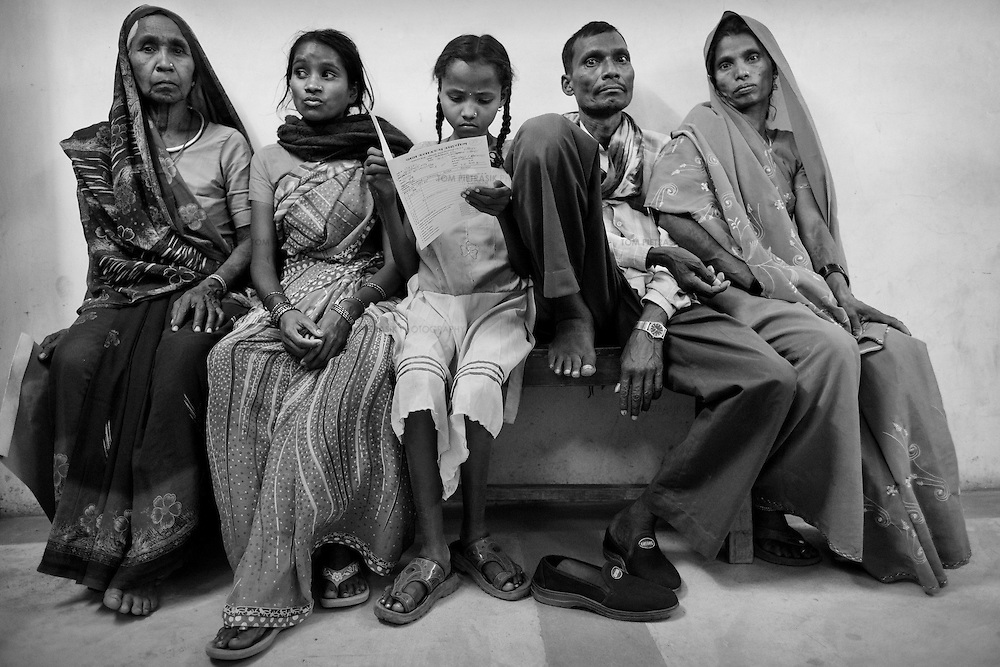 Patients wait in line during an out-patient clinic, held three times a week at the JSS hospital in Ganiyari.<br /> <br /> The JSS (Jan Swasthya Sahyog or People's Health Support Group) is a public-health initiative established in 1996 by a handful of committed doctors, all of whom trained at elite medical schools in India. While many of their peers secured high profile, high earning posts in premier hospitals in India, the US and the UK, the doctors at JSS provide a service for poor and marginalised rural communities in Bilaspur district in the eastern India.<br /> <br /> The JSS operate out of a hospital in Ganiyari, near Bilaspur. Relying on grants and donations, the JSS provide a first-class service for a community that would otherwise rely on underfunded and poorly resourced government facilities. Though JSS hospital boasts 30 beds, two operating theatres, a fully-equipped lab and three outpatient clinics a week, the service provided by JSS is over-subscribed by a community of 800,000 people from 1,500 villages. <br /> <br /> To address the malnutrition, the JSS offers training on new agricultural techniques. The JSS has a well established outreach program of village-clinics and employs over 100 village health workers serving 53 villages. They also operate an ambulance service and assist with transport costs for a community who's access to essential services has been undermined by the Chhattisgarh government's decision to completely disinvest in public transport. <br /> <br /> Continually exposed to illnesses associated with malnutrition and poverty including tuberculosis and rheumatic heart disease, the doctors at JSS are tireless advocates for universal healthcare and focus resources upon the three-quarters of India's population (over 800 million people) who live on less than 20 Rupees (50 US cents) a day. <br /> <br /> Photo: Tom Pietrasik<br /> Chhattisgarh, India. <br /> March 2010
