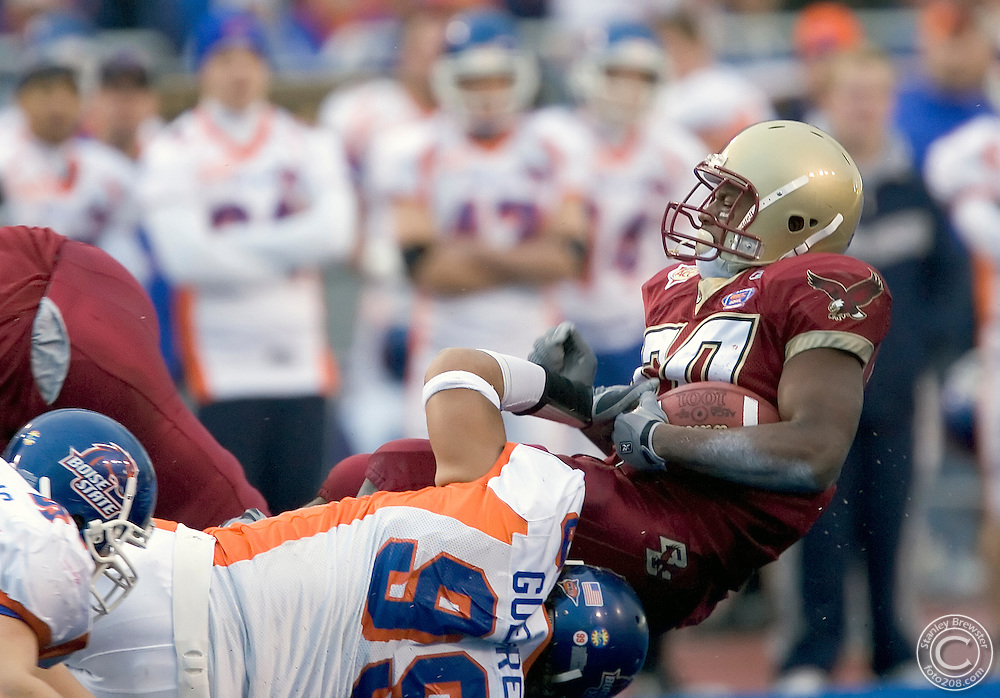 12-28-05-Boise ID. Boise State vs. Boston College in the 2005 MPC Computers Bowl in Bronco Stadium. Boise State defensive lineman Alex Guerrero (99) tackles Boston College running back L. V. Whitworth (30) for a 2 yard loss. The Eagles beat the Broncos 27-21.