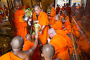 "22 JULY 2013 - PHRA PHUTTHABAT, THAILAND: Buddhist monks pray in the Mondop (chapel that houses the footprint) before the Tak Bat Dok Mai at Wat Phra Phutthabat in Saraburi province of Thailand, Monday, July 22. Wat Phra Phutthabat is famous for the way it marks the beginning of Vassa, the three-month annual retreat observed by Theravada monks and nuns. The temple is highly revered in Thailand because it houses a footstep of the Buddha. On the first day of Vassa (or Buddhist Lent) people come to the temple to ""make merit"" and present the monks there with dancing lady ginger flowers, which only bloom in the weeks leading up Vassa. They also present monks with candles and wash their feet. During Vassa, monks and nuns remain inside monasteries and temple grounds, devoting their time to intensive meditation and study. Laypeople support the monastic sangha by bringing food, candles and other offerings to temples. Laypeople also often observe Vassa by giving up something, such as smoking or eating meat. For this reason, westerners sometimes call Vassa the ""Buddhist Lent.""      PHOTO BY JACK KURTZ"