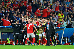 LILLE, FRANCE - Friday, July 1, 2016: Wales staff and substitutes celebrate after captain Ashley Williams scored the first equalising goal during the UEFA Euro 2016 Championship Quarter-Final match against Belgium at the Stade Pierre Mauroy. head of performance Ryland Morgans, assistant manager Osian Roberts, performance psychologist Ian Mitchall, physiotherapist Sean Connelly, goalkeeping coach Martyn Margetson, David Edwards, Andy King, Jonathan Williams, goalkeeper Daniel Ward, sports science coach Adam Owen, Ashley 'Jazz' Richards, David Cotterill, equipment manager David Griffiths, goalkeeper Owain Fon Williams, manager Chris Coleman. (Pic by David Rawcliffe/Propaganda)