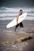 Surfer leaving the waves, Samurai Beach Port Stephens, NSW, East Coast Australia