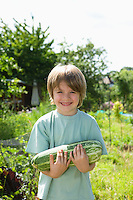 Boy holding marrow in garden portrait