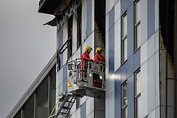 "© Licensed to London News Pictures. 16/11/2019. Bolton, UK. Firefighters examine cladding at the scene where a fire broke out overnight (15th/16th November 2019) at a block of flats known as "" The Cube "" , in Bolton Town Centre . At least two people are known to have been treated by paramedics at the scene of the six-story block , which is occupied by students of the University of Bolton . Photo credit: Joel Goodman/LNP"