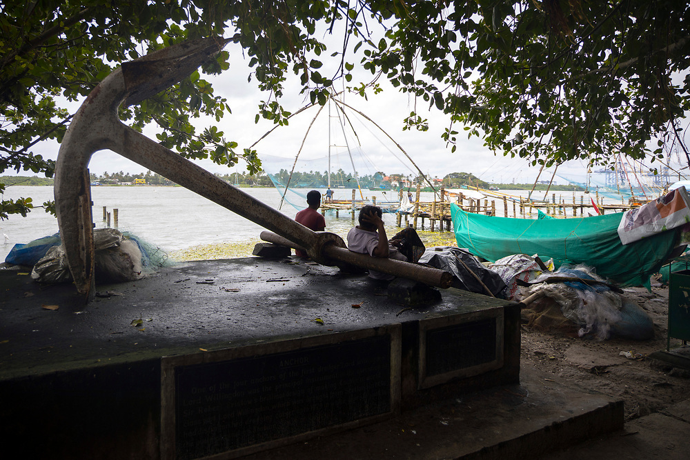 KOCHI, INDIA - 3rd September 2019 - Locals take rest in the shade under and tree and on the memorial anchor along Kochi Fort Beach and Seafront Promenade during high temperatures. Cochin, Kerala, Southern India.