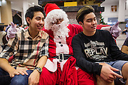 24 DECEMBER 2013 - BANGKOK, THAILAND: Thai teenagers pose with Santa Claus during Christmas observances at Holy Redeemer Church in Bangkok. Thailand is predominantly Buddhist but Christmas is widely celebrated throughout the country. Buddhists mark the day with secular gift giving but there are about 300,000 Catholics in Thailand who celebrate religious Christmas. Catholics first came to Thailand (then Siam) in 1567 as chaplain for Portuguese mercenaries in the employ of the Siamese monarchy. There has been a continuous Catholic presence in Thailand since then.   PHOTO BY JACK KURTZ