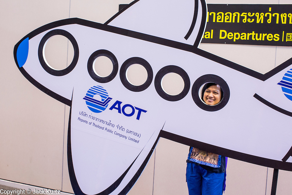 01 OCTOBER 2012 - BANGKOK, THAILAND:  A person poses in a cutout of an airplane in the departure hall at Don Mueang International Airport during grand reopening ceremonies Monday. Don Mueang International Airport is the smaller of two international airports serving Bangkok, Thailand. Suvarnabhumi Airport, opened in 2006 is the main one. Don Mueang was officially opened as a Royal Thai Air Force base on 27 March 1914 and commercial flights began in 1924. Don Mueang Airport closed in 2006 following the opening of Bangkok's new Suvarnabhumi Airport, and reopened as a domestic terminal for low cost airlines after renovation on 24 March 2007. Closed during the flooding in 2011, Don Mueang was again renovated and reopened in 2012 as the airport for low cost airlines serving both domestic and international passengers. On Monday, Air Asia, Asia's leading low cost airline, transferred all of their flight operations to Don Mueang and the airport was officially reopened. Suvarnabhumi International Airport is already over capacity and Don Mueang's importance as a hub is expected to grow.   PHOTO BY JACK KURTZ