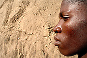 Benin, Natitingou April 22, 2005 - Young man with scarifications on his face in front a the wall of his house
