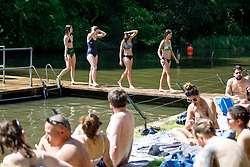 © Licensed to London News Pictures. 06/05/2018. London, UK. People swim in Hampstead Heath Mixed Bathing Pond in north London as temperatures hit 27C on Sunday, May 6, 2018. Photo credit: Tolga Akmen/LNP