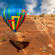 A lone, colorful hot air balloon flies close to the canyon walls and casts its shadow at Red Rock Park during the Red Rock Balloon Rally in Gallup, New Mexico.