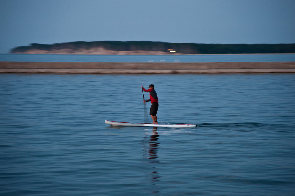 A stand up paddleboard paddler with motion blur during a workout on Lake Superior at Grand Marais Michigan.