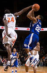Virginia guard/forward Mamadi Diane (24) disrupts a shot attempt by Hampton guard Christopher Tolson (22).  The Virginia Cavaliers defeated the Hampton Pirates 74-48 at the John Paul Jones Arena on the Grounds of the University of Virginia in Charlottesville, VA on December 23, 2008. (Special to the Daily Progress / Jason O. Watson)
