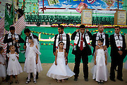 Hamas policemen stand with their and their brides younger sisters and cousins during a mass wedding for 55 policemen sponsored by Hamas party August 02, 2007 in Jabaliya camp in Gaza.  Each groom was given $500 (U.S. dollars) from Hamas and $100 from Ismail Haniya as well as the free public wedding party. Hamas cements much of its' popularity by sponsoring community events such as this as well as providing free summer camps for kids, organizing trash pickups and food distributions across Gaza.