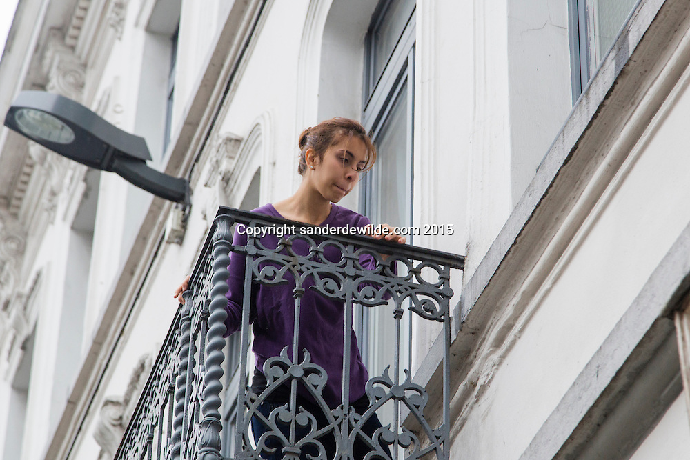 2015 november 16. Brussels, Belgium, Sint Jans Molenbeek.A female family member outside on the balcony
