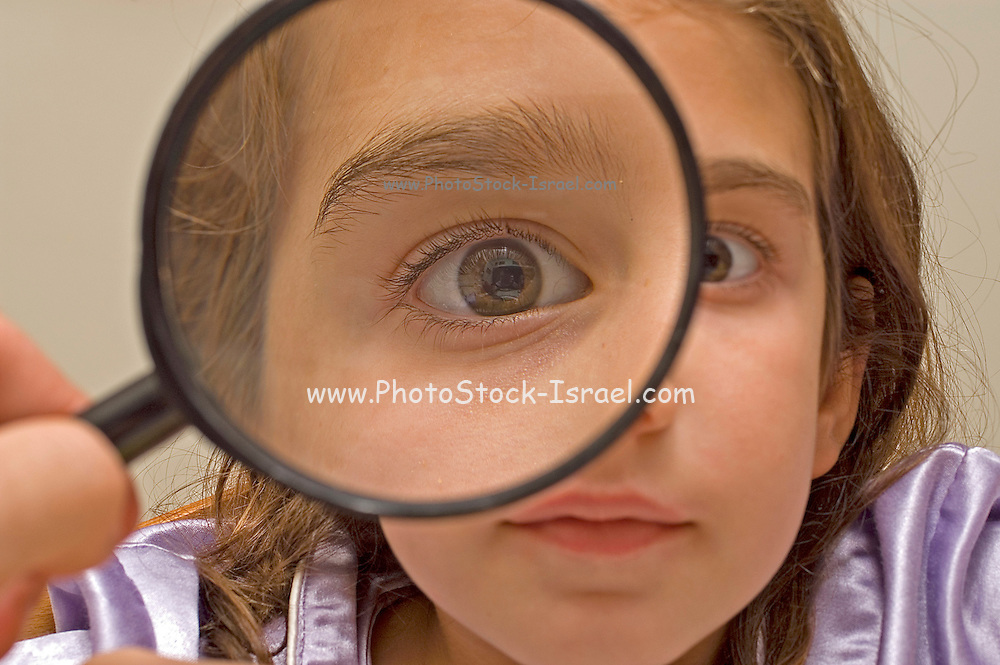 Young girl of 7 fooling around with a magnifying glass