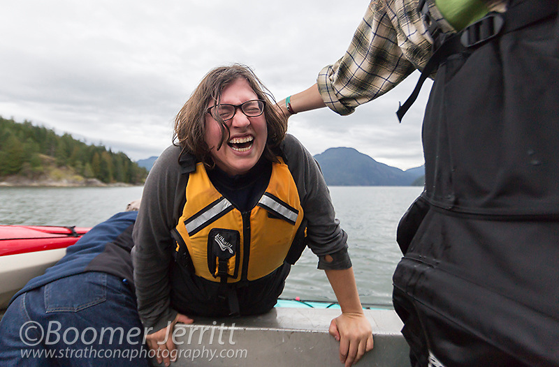 A laughing kayaker gets stuck in her kayak while trying to exit her boat.  Quadra Island, Discovery Islands, British Columbia, Canada