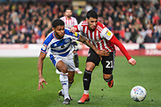 Brentford Forward Said Benrahma (21) and Queens Park Rangers Defender Darnell Furlong (2) battle for the ball during the EFL Sky Bet Championship match between Brentford and Queens Park Rangers at Griffin Park, London, England on 2 March 2019.