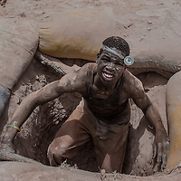 "Nobsin, Burkina Faso - 13 May 2014: Yameogo Salifu, 21, comes back to the surface after digging in a 25 meters tunnel for 4 hours. In the village where he was born, 31 km from the site, he was a farmer but could not afford to make a living. He says ""I started searching for gold 6 months ago. Down in the tunnels is pitch black and hot, but I have no fear. Survival is there."""
