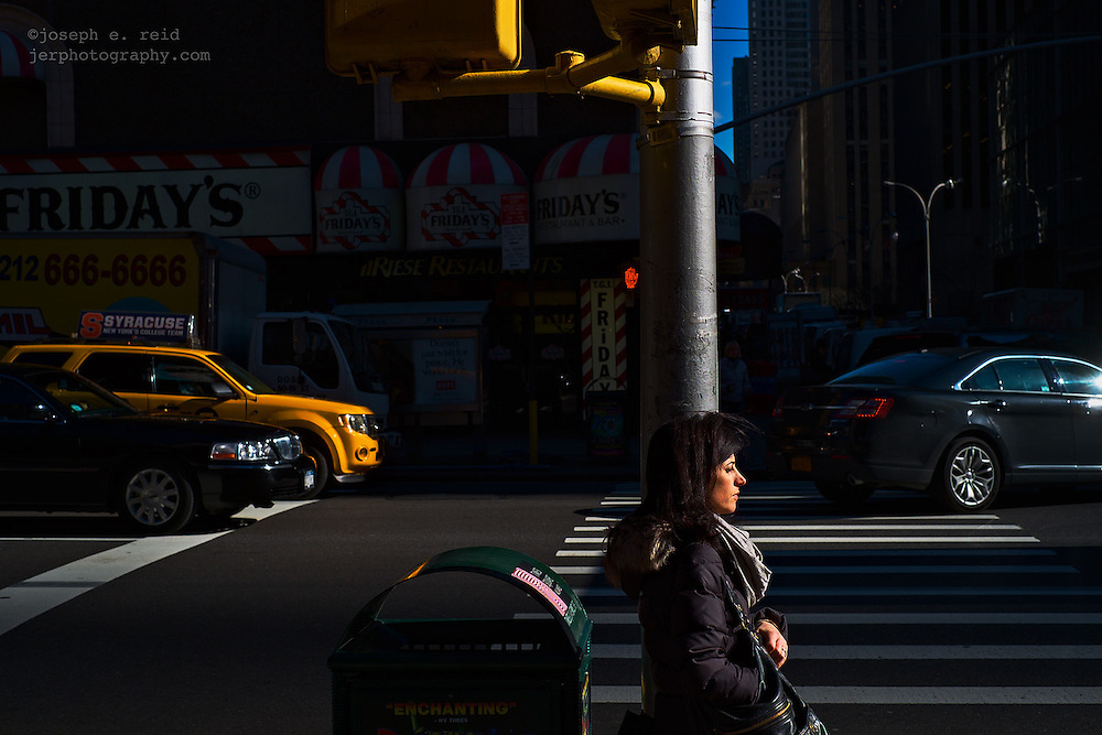 Woman leaning against pole at intersection