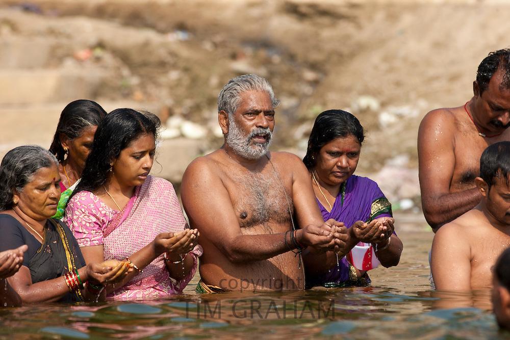 Indian Hindu men and women bathing and praying in the River Ganges by Kshameshwar Ghat in holy city of Varanasi, India