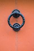 Black metal door knocker on salmon coloured door