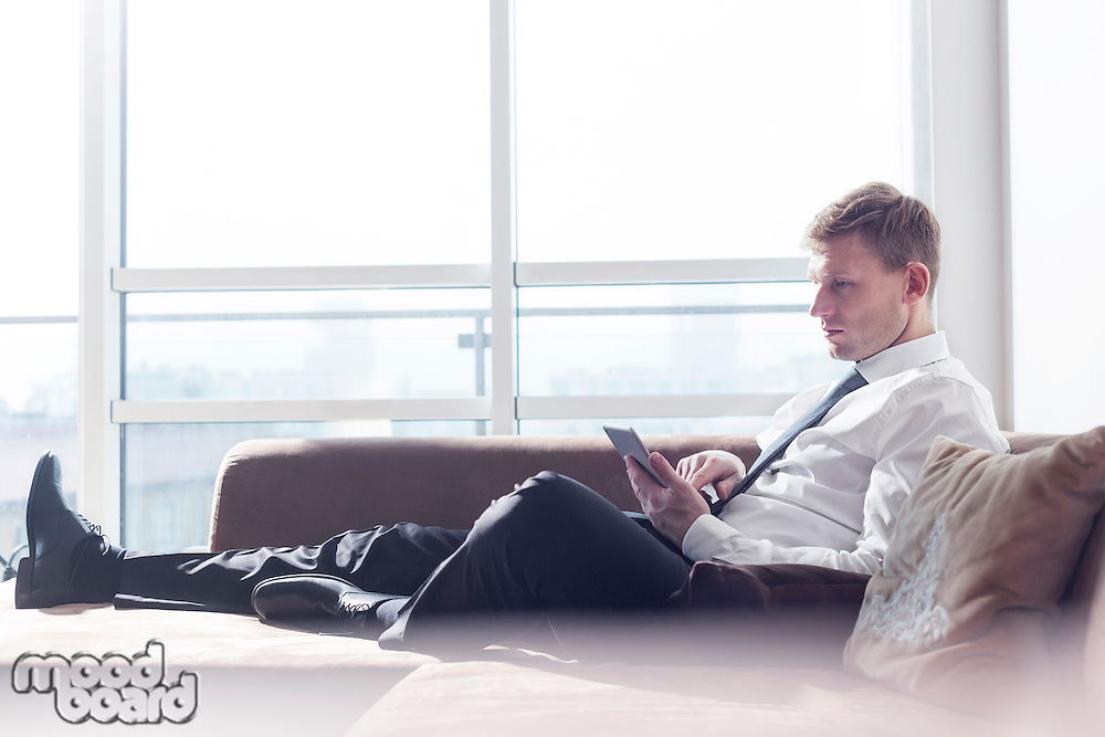 Full length of businessman using digital tablet on sofa at home