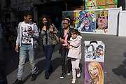 Street portrait caricatures and construction artwork faces in Leicester Square in central London.