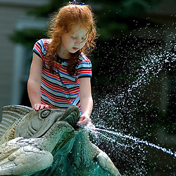 Sara Graca..6-year-old Caitie Williams discovered a new way to play with the fountain in Bestor Plaza when she discovered she could hols a penny up to the fish's mouth and it would spew its stream everywhere.