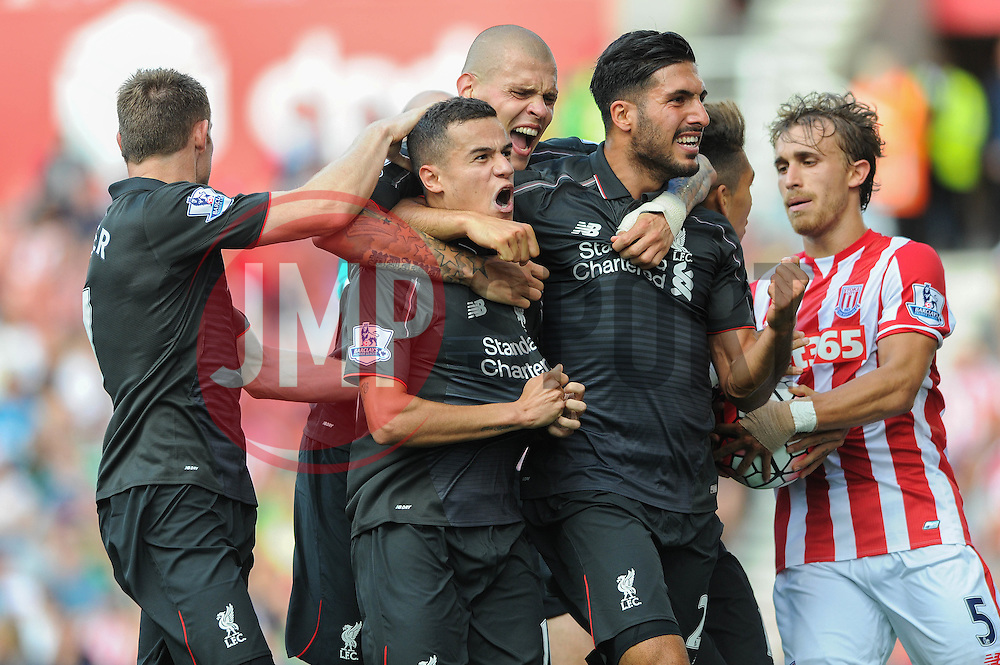 Philippe Coutinho of Liverpool celebrates with his team mates after scoring as Marc Muniesa of Stoke City attempts to take the ball from Roberto Firmino of Liverpool - Mandatory byline: Dougie Allward/JMP - 07966386802 - 09/08/2015 - FOOTBALL - Britannia Stadium -Stoke-On-Trent,England - Stoke City v Liverpool - Barclays Premier League