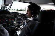 "Pilot, Danielle Aitchison, and her partner Captain Chris Hood taxi the UNHAS Beechcraft 1900D past a US Airforce C-130 at Kabul International Airport.  Danielle flies in Afghanistan for The United Nations Humanitarian Air Service (UNHAS).   ...When asked about flying in a war zone, she says,  ""I'm just a normal average female.  My job is maybe a little different to some, but I have the same feminine side as other women.  I don't have any trouble going back to New Zealand relating to people.  I'm just a regular chick.""."