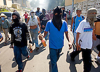 A men wearing masks and carrying Molotov cocktails march down a street as they demonstrate in the street Tuesday Sept. 11, 2007, Palin Guatemala. A angry mob took to the streets and went on to burn down the mayors office as well as his home in demonstration after and clash with local police on the previous day. Residents accuse the mayor of, among other things, of bussing voters for the elections on Sept. 9 2007.   (photo by/ Darren Hauck).........