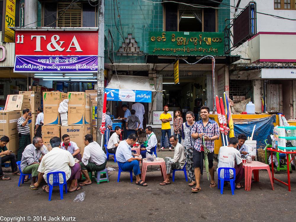 01 NOVEMBER 2014 - YANGON, MYANMAR: A tea stand in front of an electronics shop in Yangon, Myanmar.    PHOTO BY JACK KURTZ