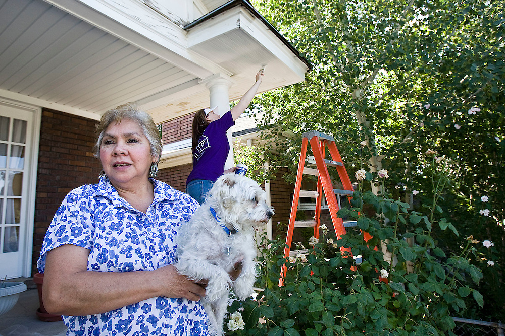 Amanda Molina holds her dog Willow on the front steps of her home as volunteer Kelly Weight-Allred of Saratoga Springs helps paint her home as she participates in the annual Paint Your Heart Out 2010 event in Salt Lake City, Utah, Saturday, Aug. 14, 2010. (August Miller, Deseret News).