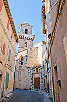 Looking up at an ancient church tower down an alley in the historic city of Arles, France.