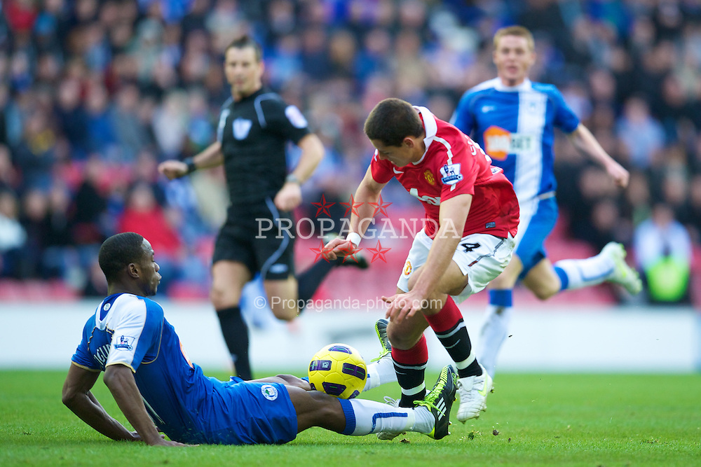 WIGAN, ENGLAND - Saturday, February 26, 2011: Manchester United's Javier Hernandez and Wigan Athletic's Maynor Figueroa during the Premiership match at the DW Stadium. (Photo by David Rawcliffe/Propaganda)