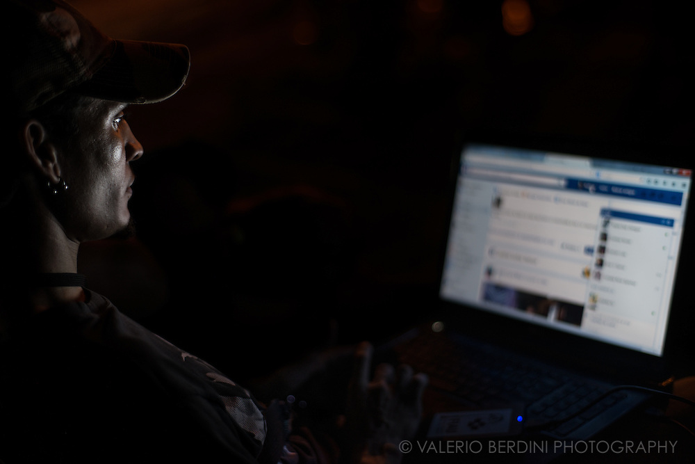 A man lit up by his laptop screen set on a Facebook page on a bench of Parque Fe del Valle in Havana, Cuba, on the night of 28 December 2015. Since the arrive of wi-fi hotspots, Facebook has been on of the main attractions for the young Cuban generation. Contrary to skype and other videocall services,  the site is freely accessible. This man was aware of the photographer, but he continued using his computer regardless. This photo was not staged.