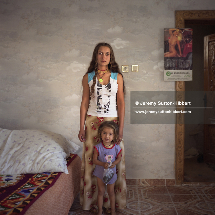 "Cassinca, a young Roma woman, stands with her daughter in one of the rooms of her new house. For the photograph Cassinca has taken off her headscarf which shows she is married, and let her hair down, to be more ""Western"" in appearance..."